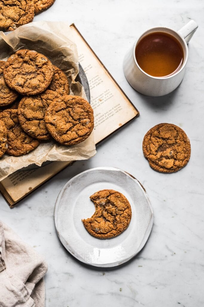 Cookies on a dish with book, tea and plate nearby on a marble surface