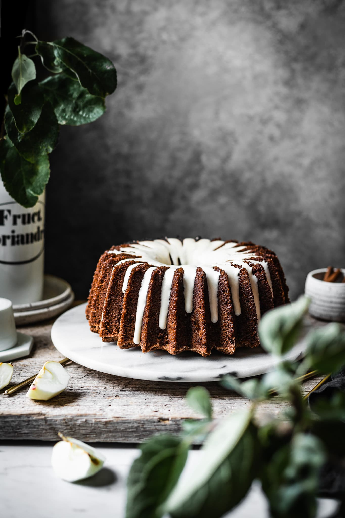 Brown bundt cake with white glaze on a marble platter with apple branches in foreground