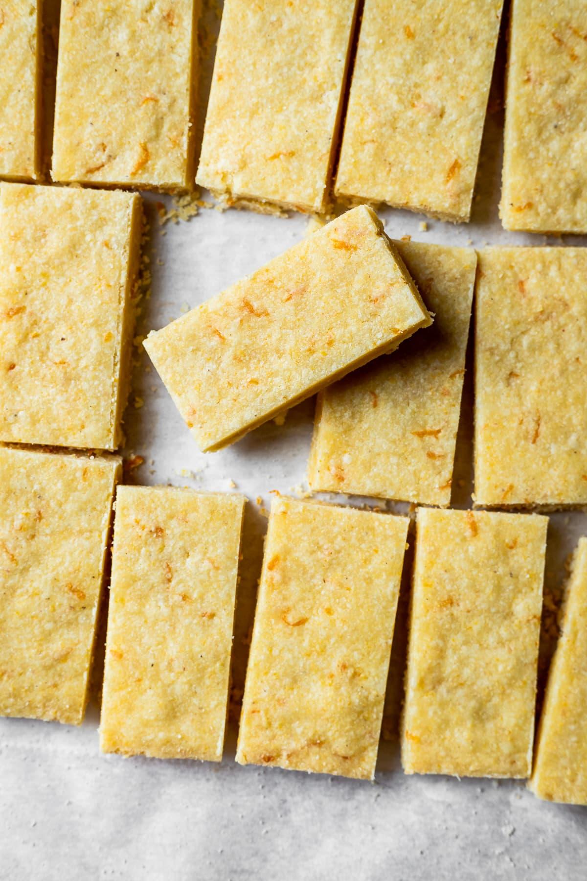 Shortbread cookies with orange zest cut into rectangles on white parchment paper
