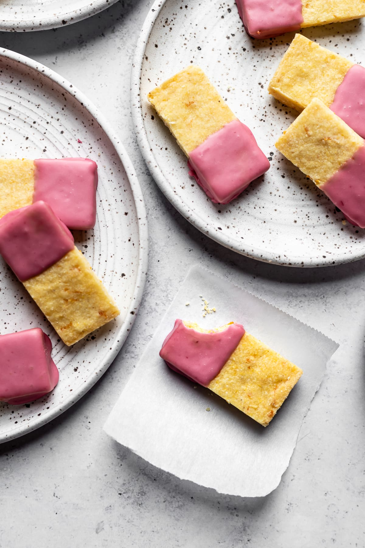 Glazed shortbread bars on white speckled plates with a bite taken out of one bar