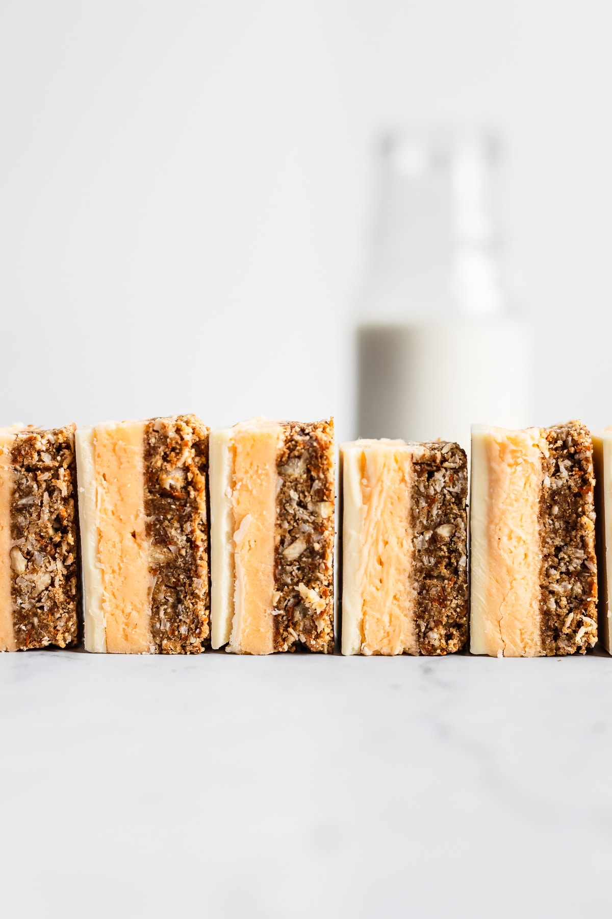 A row of sliced carrot cake bars turned on their side and lined up like dominos on a white marble surface with a glass bottle of milk in the background
