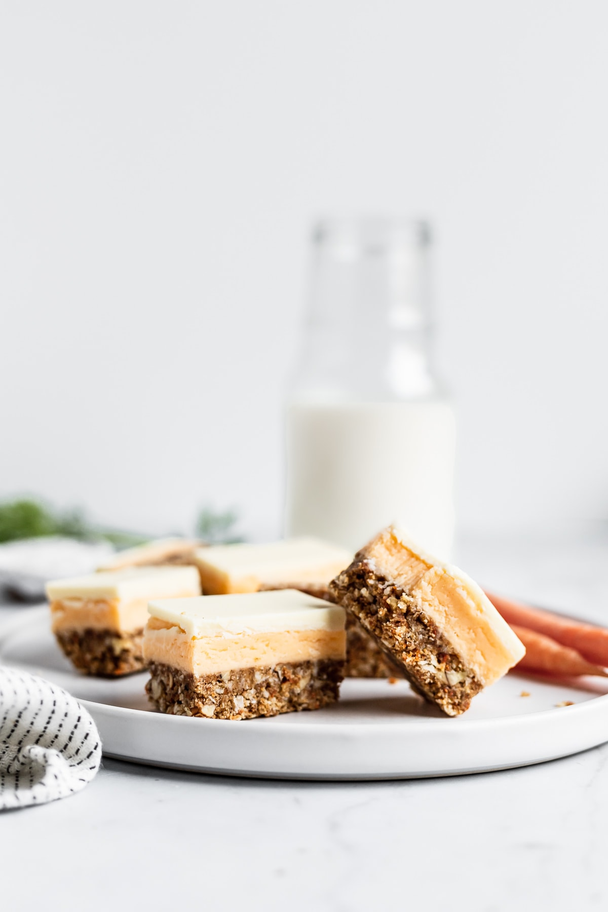 Sliced carrot cake bars on a white plate with a glass milk bottle in the background