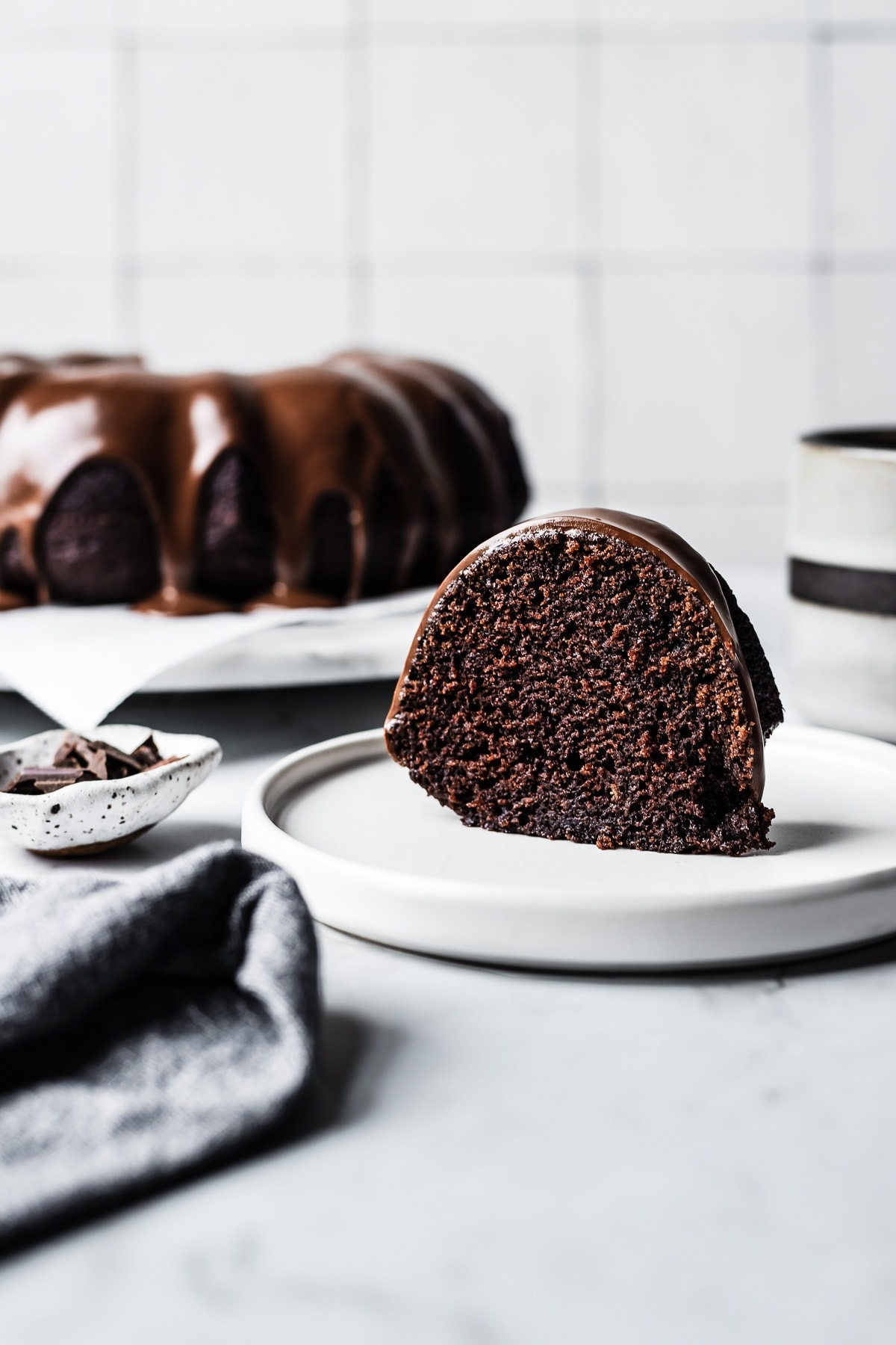 Slice of chocolate olive oil bundt cake on a white plate and marble counter with whole cake on platter in the background