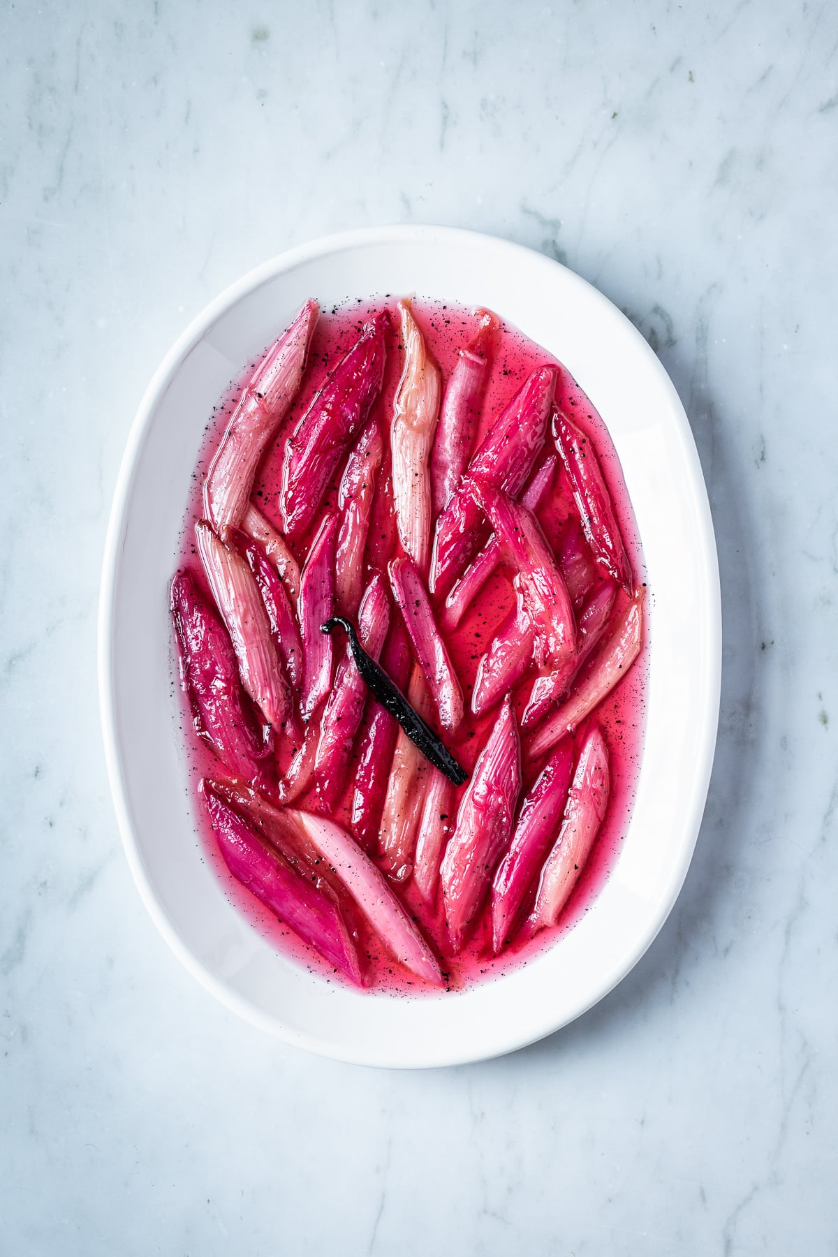 Bright pink poached rhubarb on a white oval platter on a grey marble surface