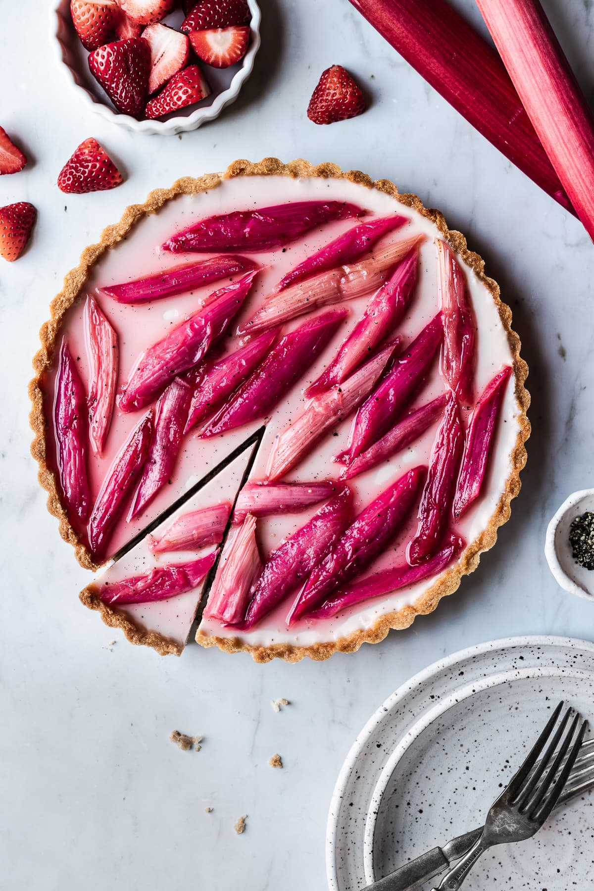 Strawberry rhubarb panna cotta tart with a slice cut into it on a grey marble background with strawberries, rhubarb and plates nearby