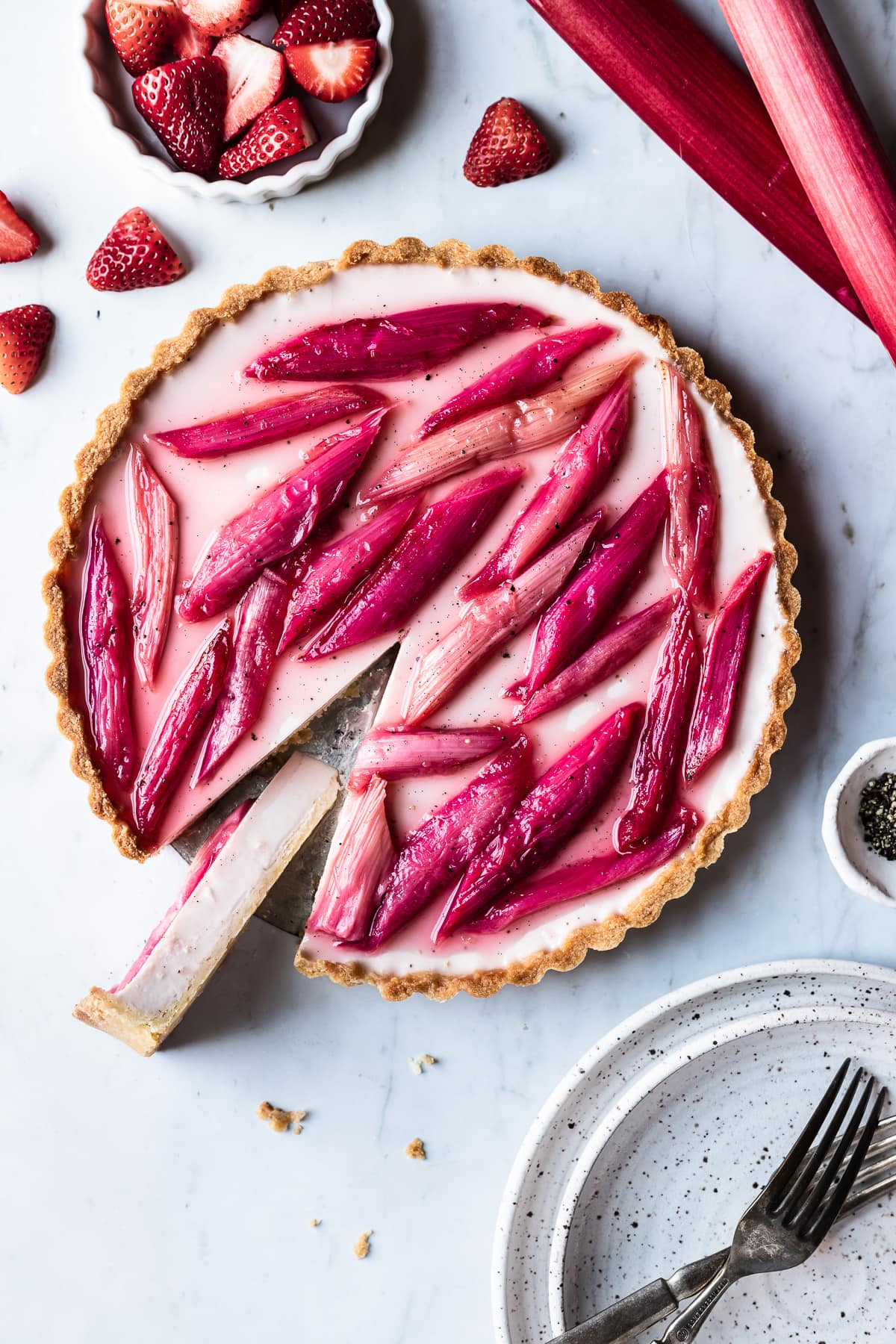Strawberry rhubarb panna cotta tart with a slice cut out and turned sideways to see the filling