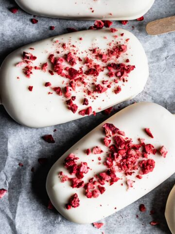 Closeup of strawberry rhubarb ice cream bars covered in white chocolate with freeze dried strawberry bits sprinkled on top