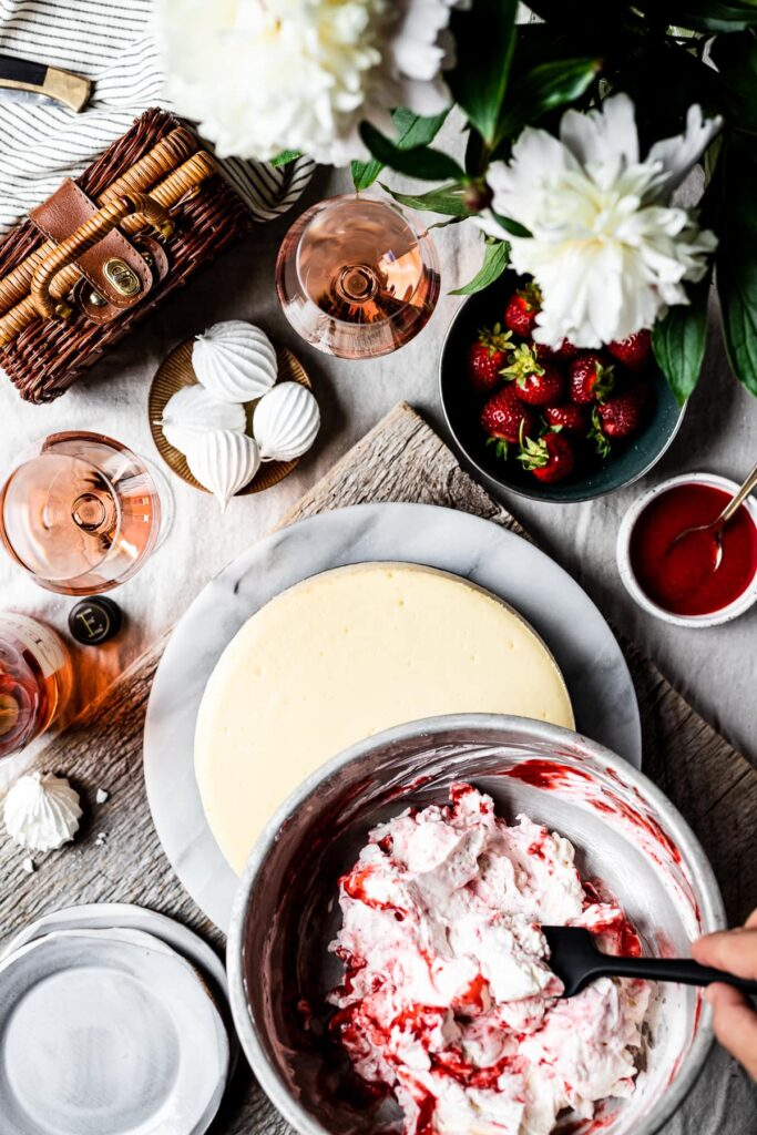 Top view of whipped cream meringue topping being placed onto the cheesecake. The cheesecake rests on a marble platter on a rustic wooden board. It looks like a picnic scene with a blanket, basket, pocketknife and flowers nearby.