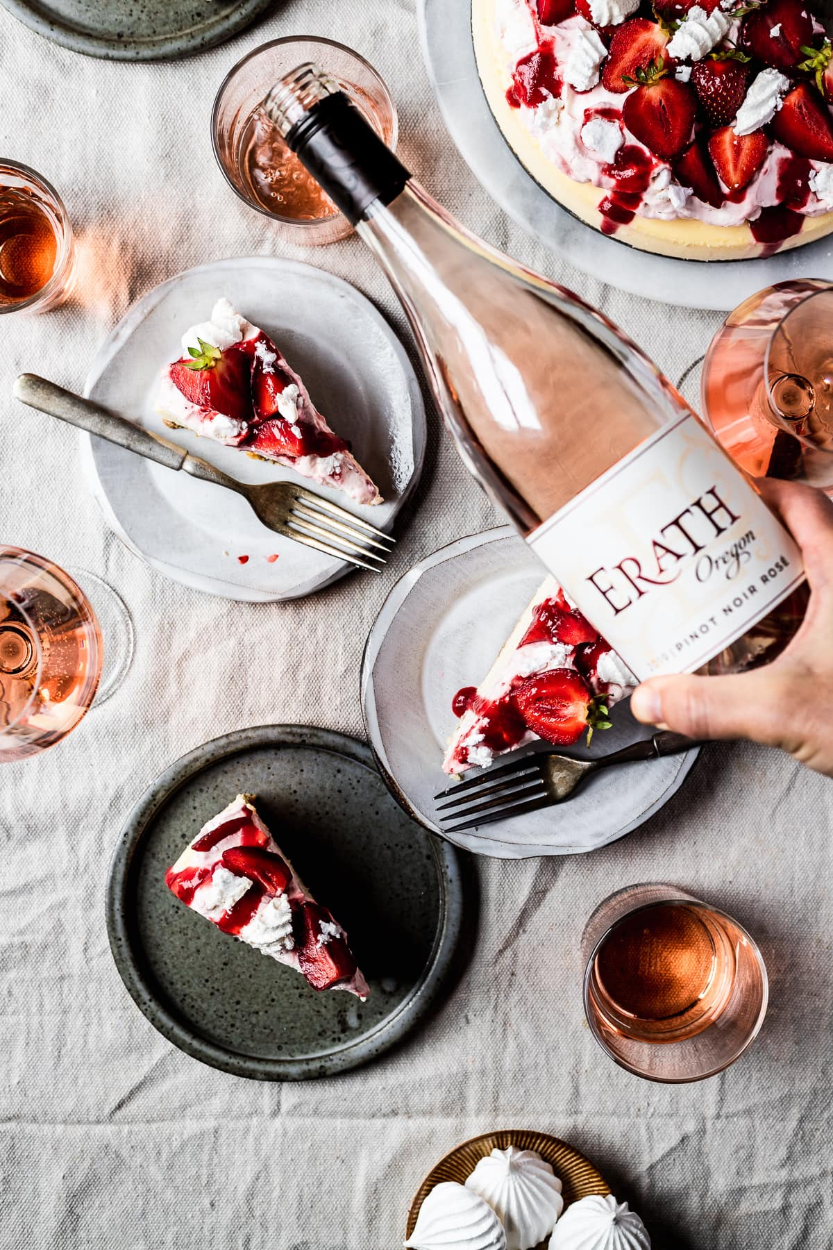 A summery picnic scene with slices of strawberry eton mess cheesecake on plates. A hand pours a bottle of rosé wine into a glass.