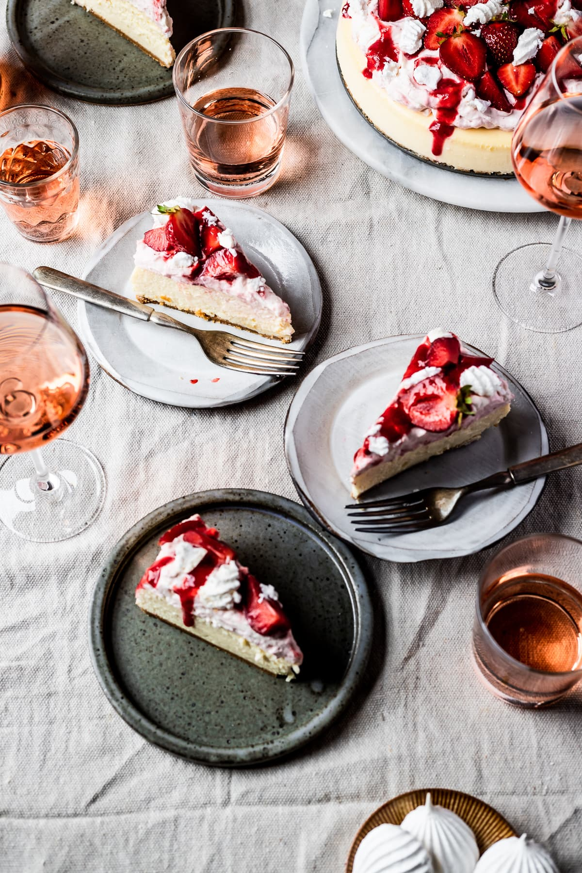 A picnic scene with slices of cheesecake on plates on a linen cloth with glasses of rosé wine nearby.