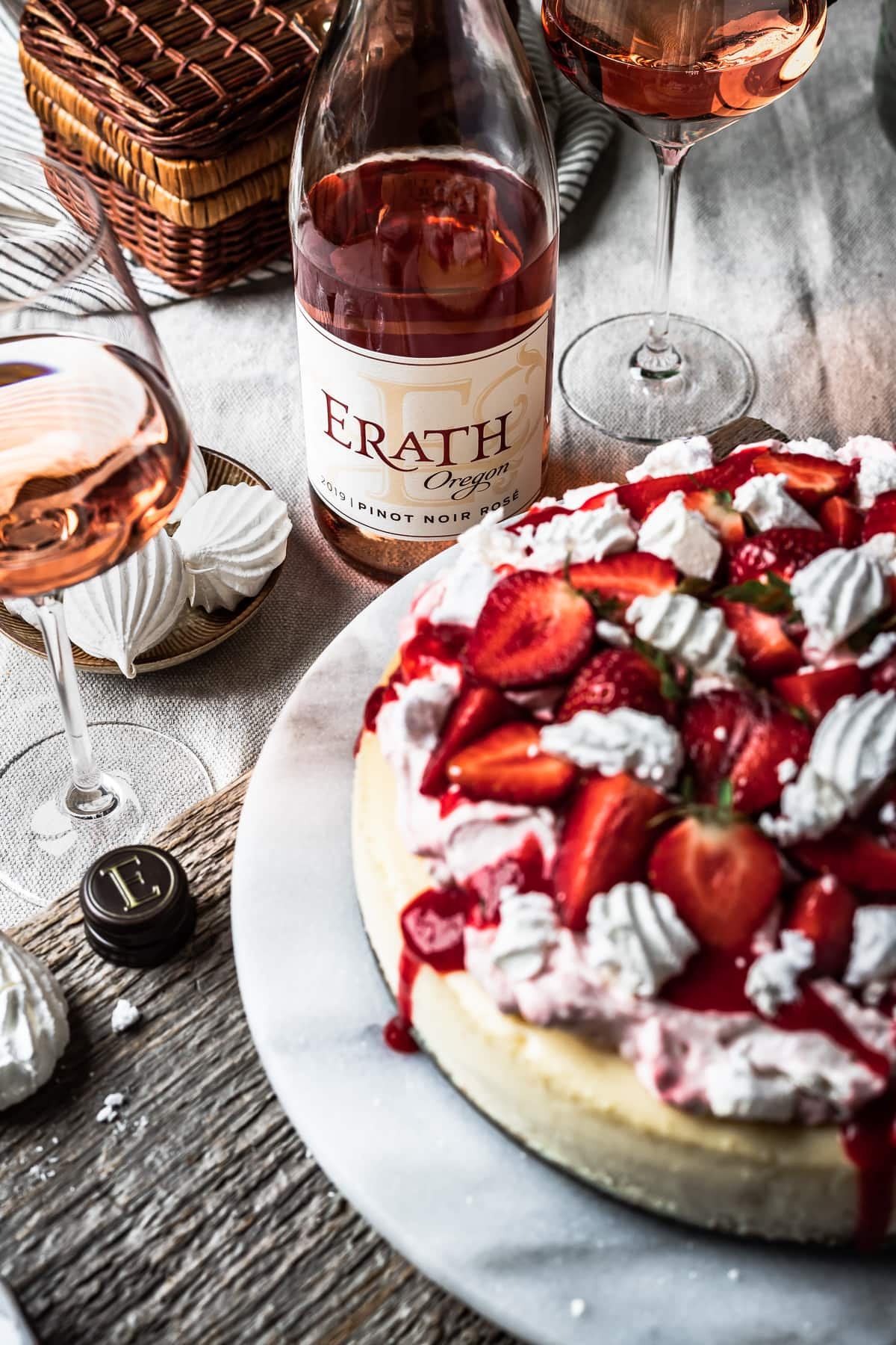 A picnic scene focused a close up of the rosé bottle and the wine in two glasses. An out of focus strawberry cheesecake peeks into the foreground.