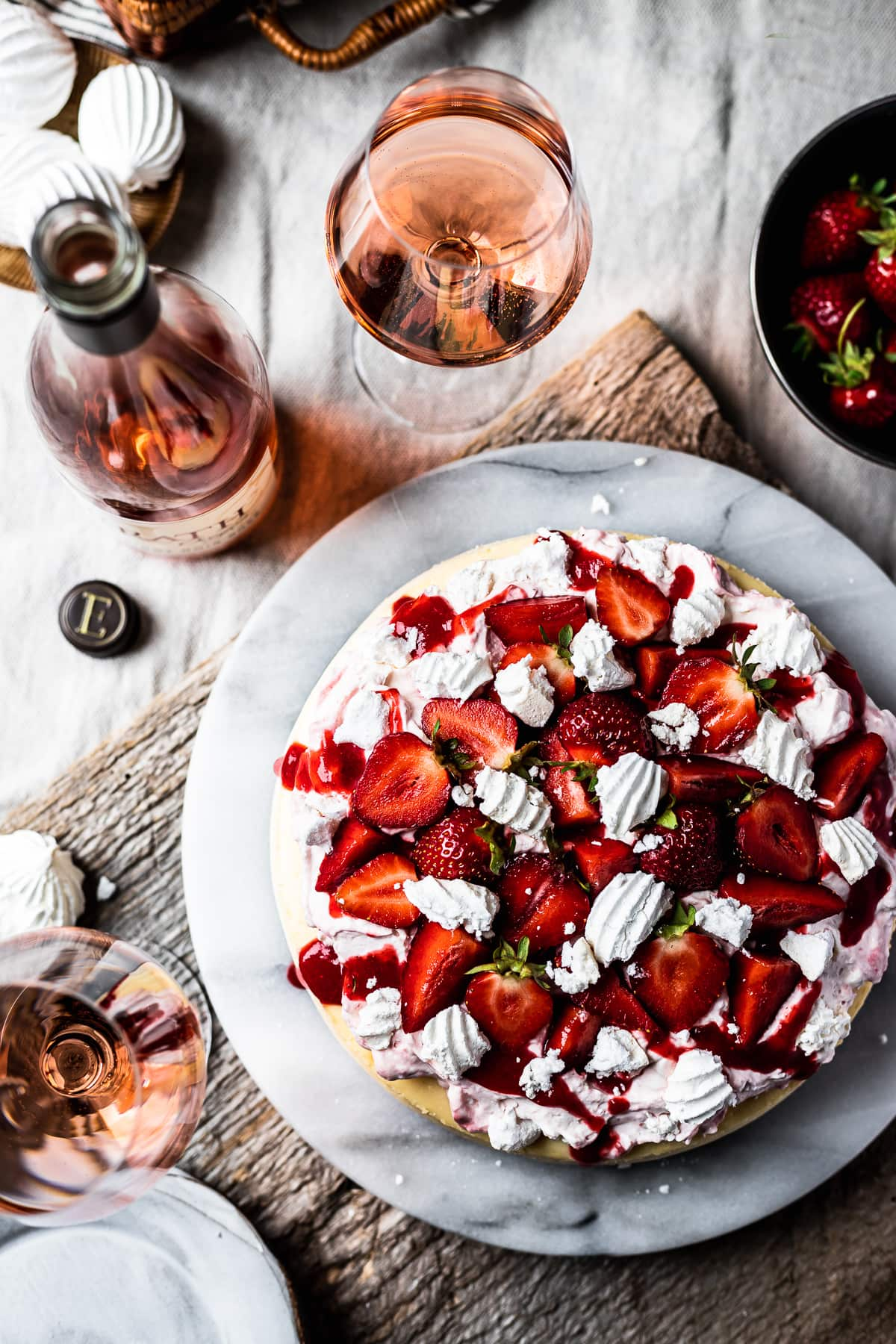 Top view of strawberry topped cheesecake on a marble platter. A rustic wooden board serves as a background. Glasses of rosé wine and a wine bottle rest nearby.