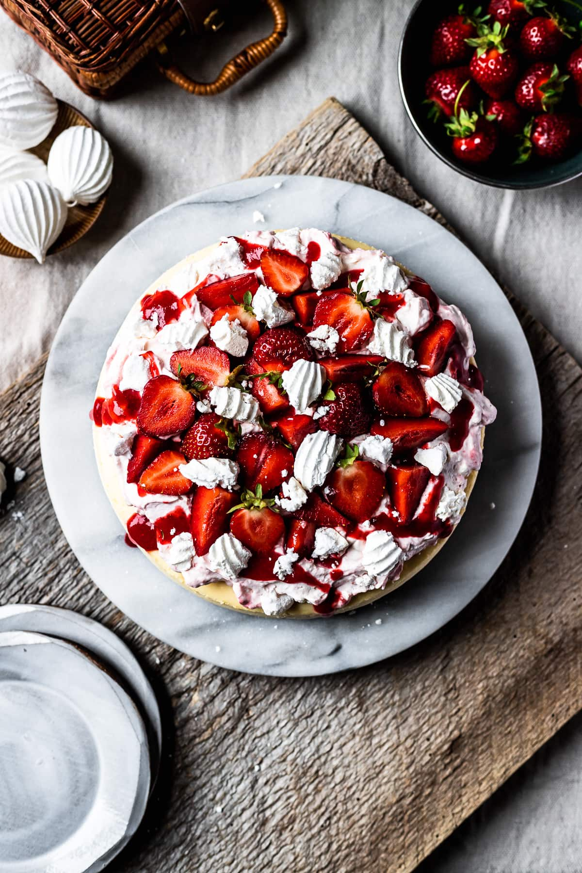 Top view of strawberry topped cheesecake on a marble platter. A rustic wooden board serves as a background. A bowl of fresh strawberries sits nearby.