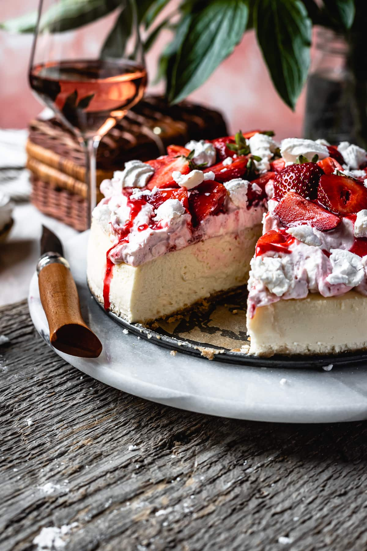 Side view of cheesecake with a slice cut out of it, revealing the creamy interior. The cheesecake is topped with whipped cream, strawberries and meringues.