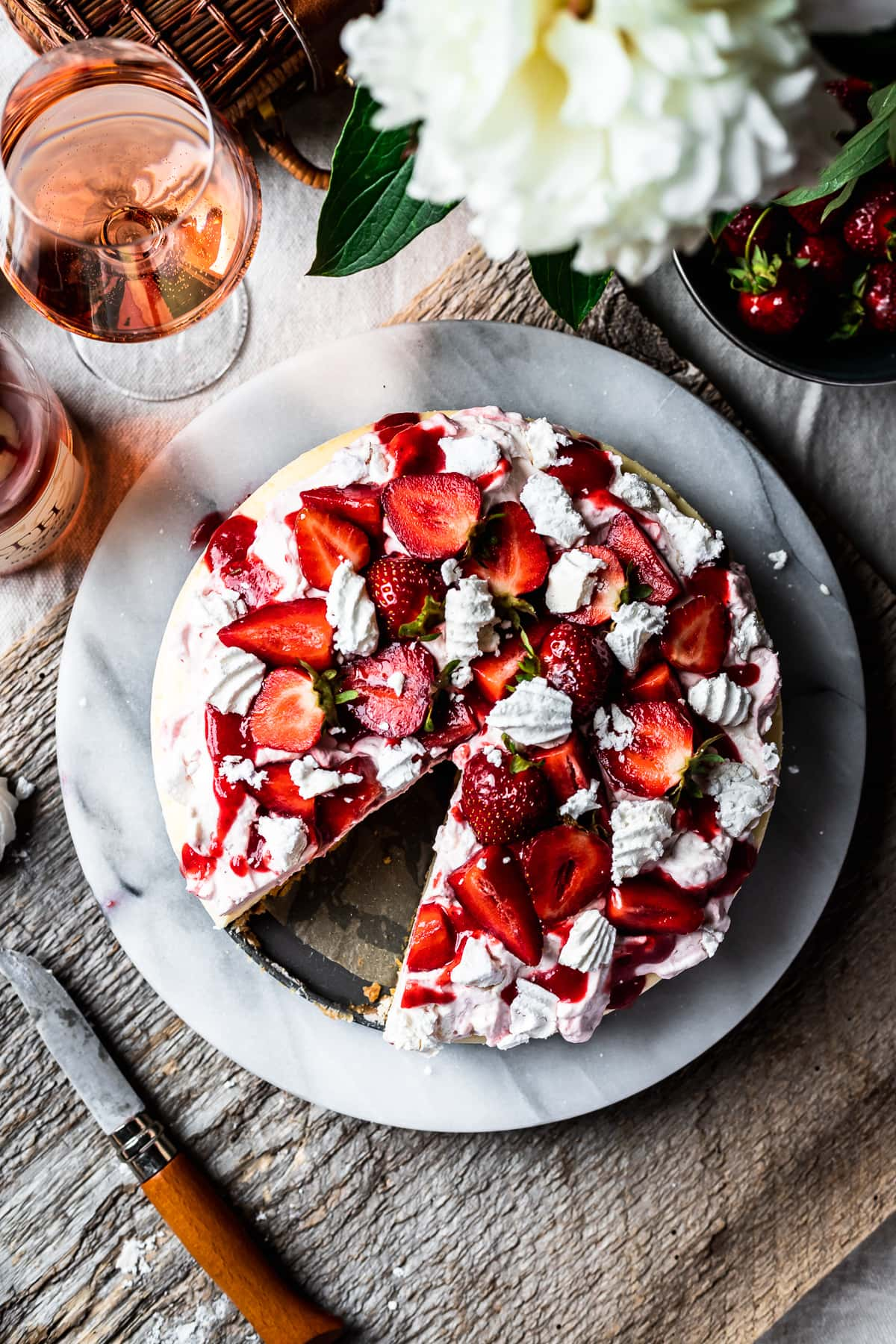 Top view of strawberry topped cheesecake with a slice missing. A rustic wooden board serves as a background. A glass of rosé wine sits nearby.