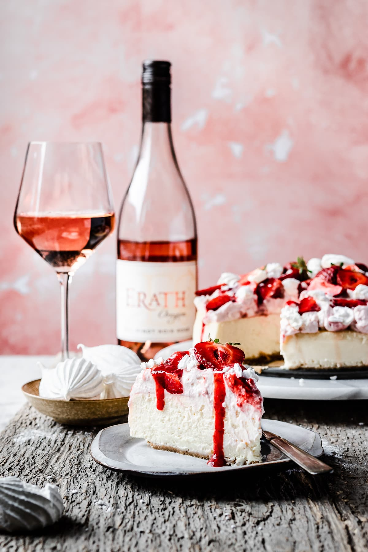 A slice of strawberry eton mess cheesecake on a plate with the remainder of the cheesecake in the background. A glass of rosé wine and a wine bottle sit nearby. The image has a pale pink background.