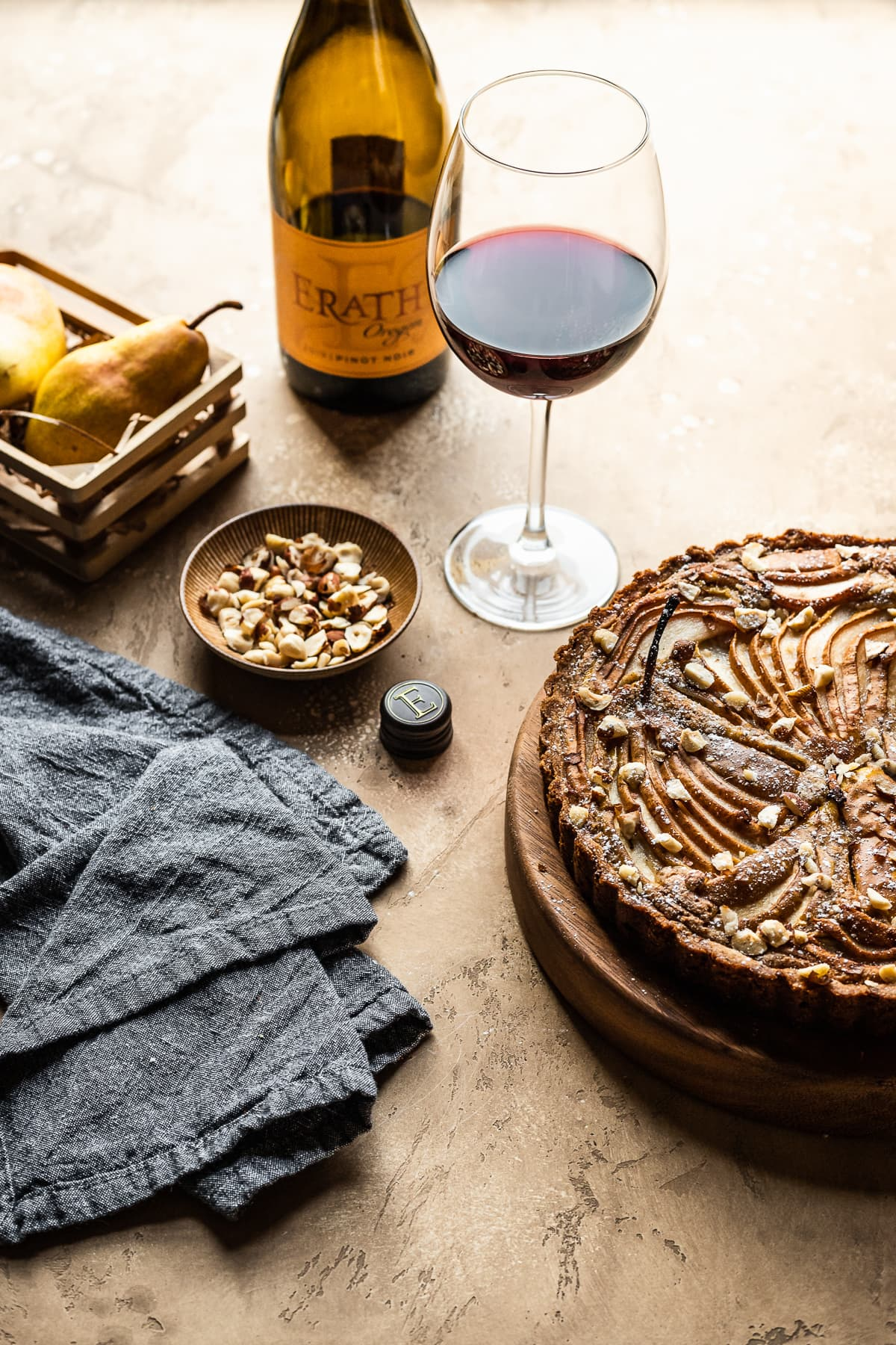 A pear tart on a wooden platter on a warm tan textured background. Nearby is a small bowl of nuts, a grey textured napkin, a small wooden crate of pears, and a glass of red wine with bottle.