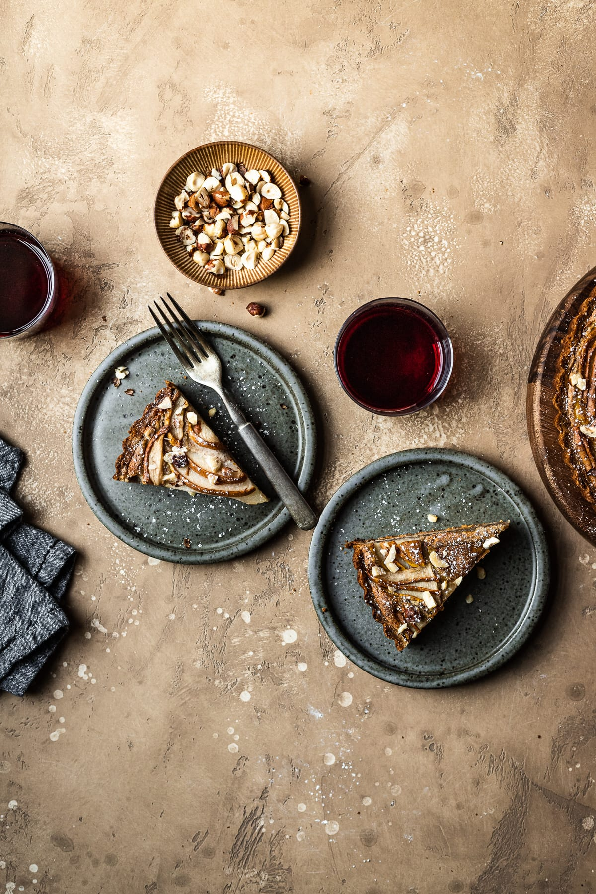 Two slices of tart on speckled grey blue ceramic plates. To the right is the remainder of the tart. A small bowl of hazelnuts, and two stemless wine glasses filled with red wine surround the plates. A grey textured linen napkin is at lower left. The background of the image is a warm tan speckled stone.