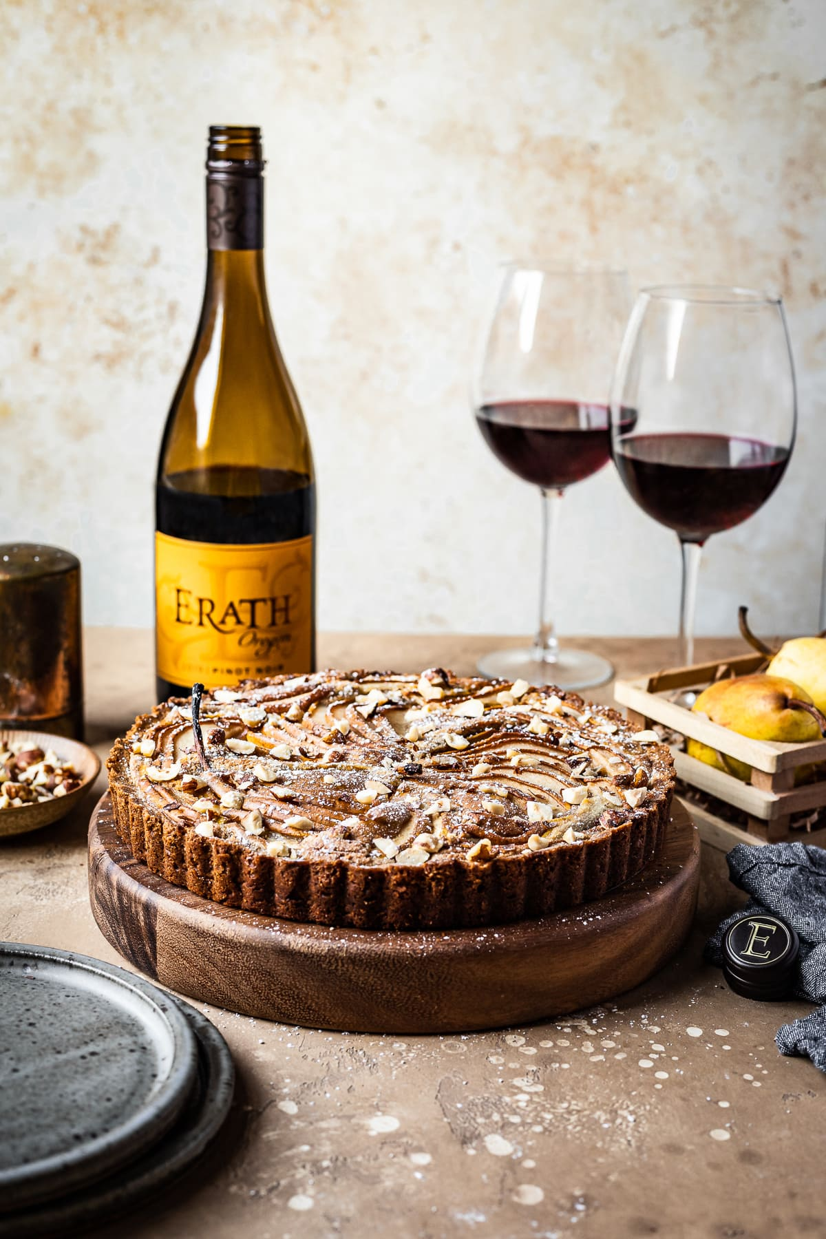 A front view of a pear tart on a round wooden platter on a textured warm tan background. The tart is surrounded by blue grey ceramic plates, an opened bottle of red wine, two half full glasses of red wine, a small wooden crate of pears, and a textured grey napkin.