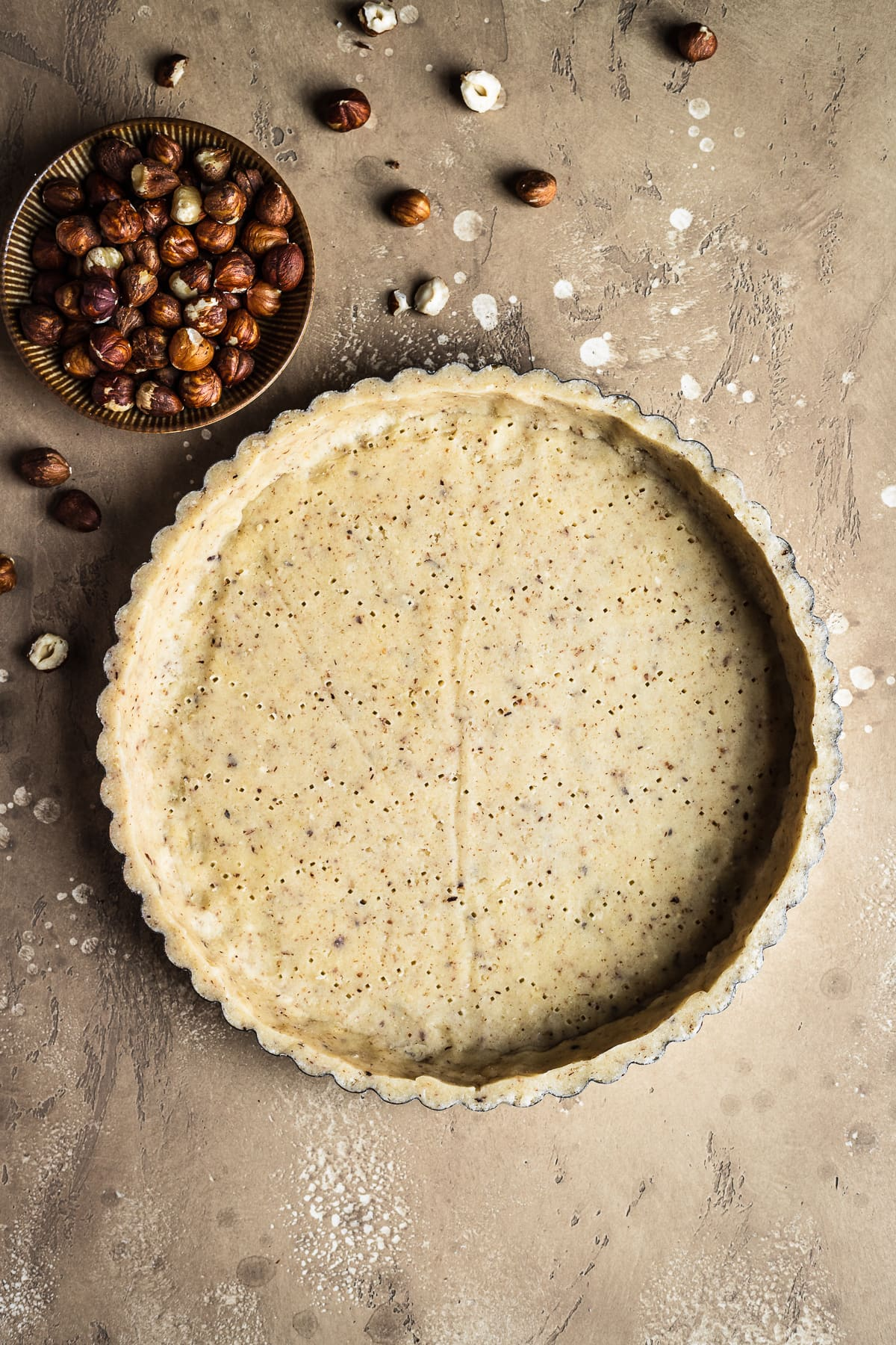 An unbaked round tart crust with a small bowl of hazelnuts at top left, resting on a textured speckled tan background.