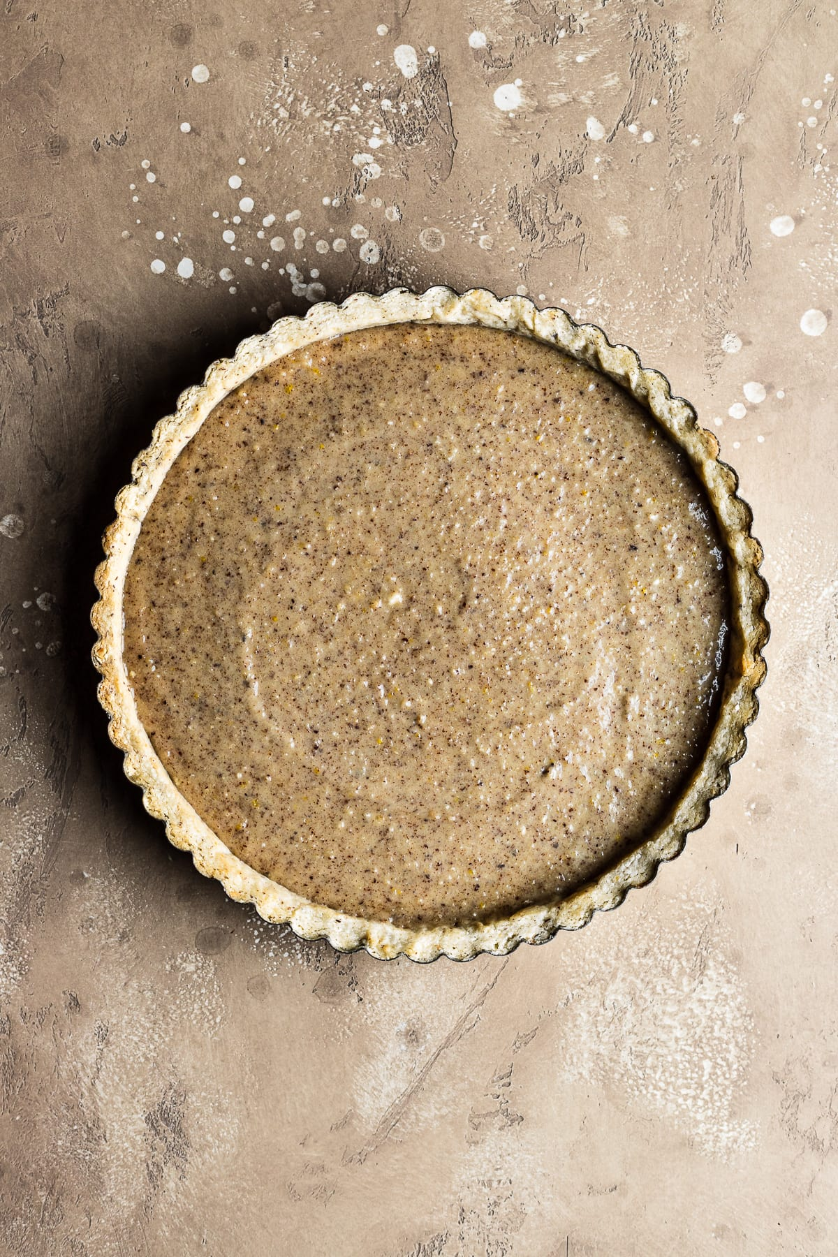 A blind baked round tart crust filled with hazelnut frangipane resting on a textured speckled tan background.