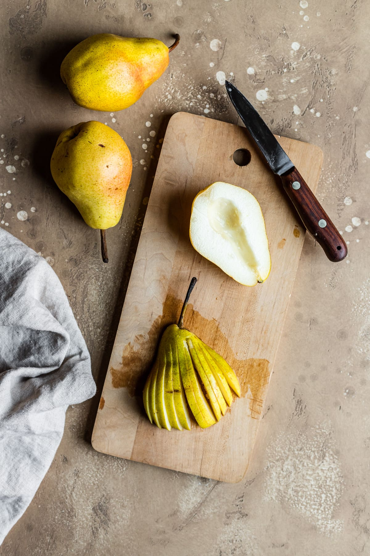 A wooden cutting board with two pear halves resting on it. One is face up with the core removed, and another is face down and has been cut into a fan shape with thin slices but the top of the pear intact. A wooden knife rests on the board, and two whole pears are at top left. A pale linen napkin is at bottom left. The scene has a textured tan stone background.