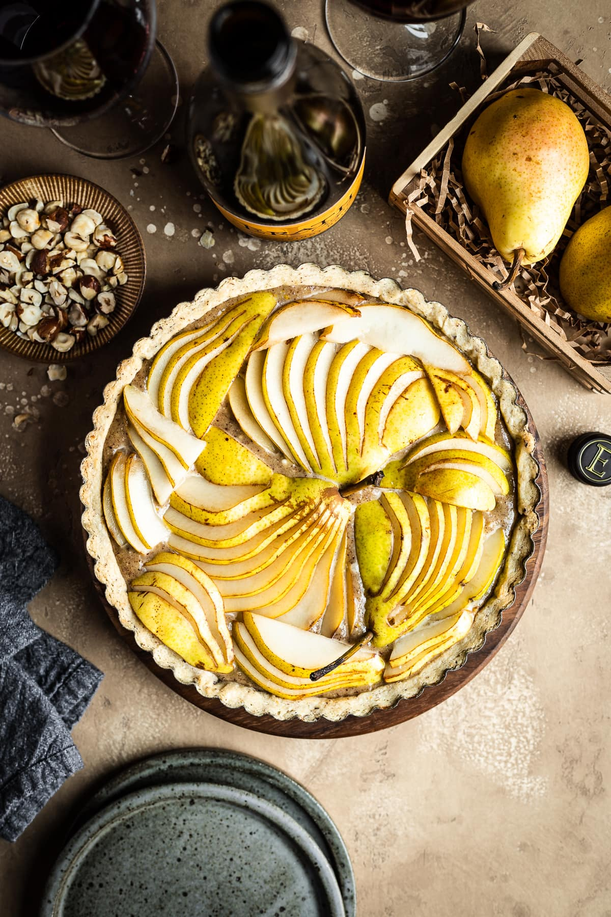 An unbaked pear hazelnut tart in a round pan is at the center of the image. Surrounding the tart are speckled blue ceramic plates, a bowl of chopped hazelnuts, pears in a wooden crate, a linen napkin, and a bottle of red wine with two filled wine glasses. Everything rests on a textured tan background.