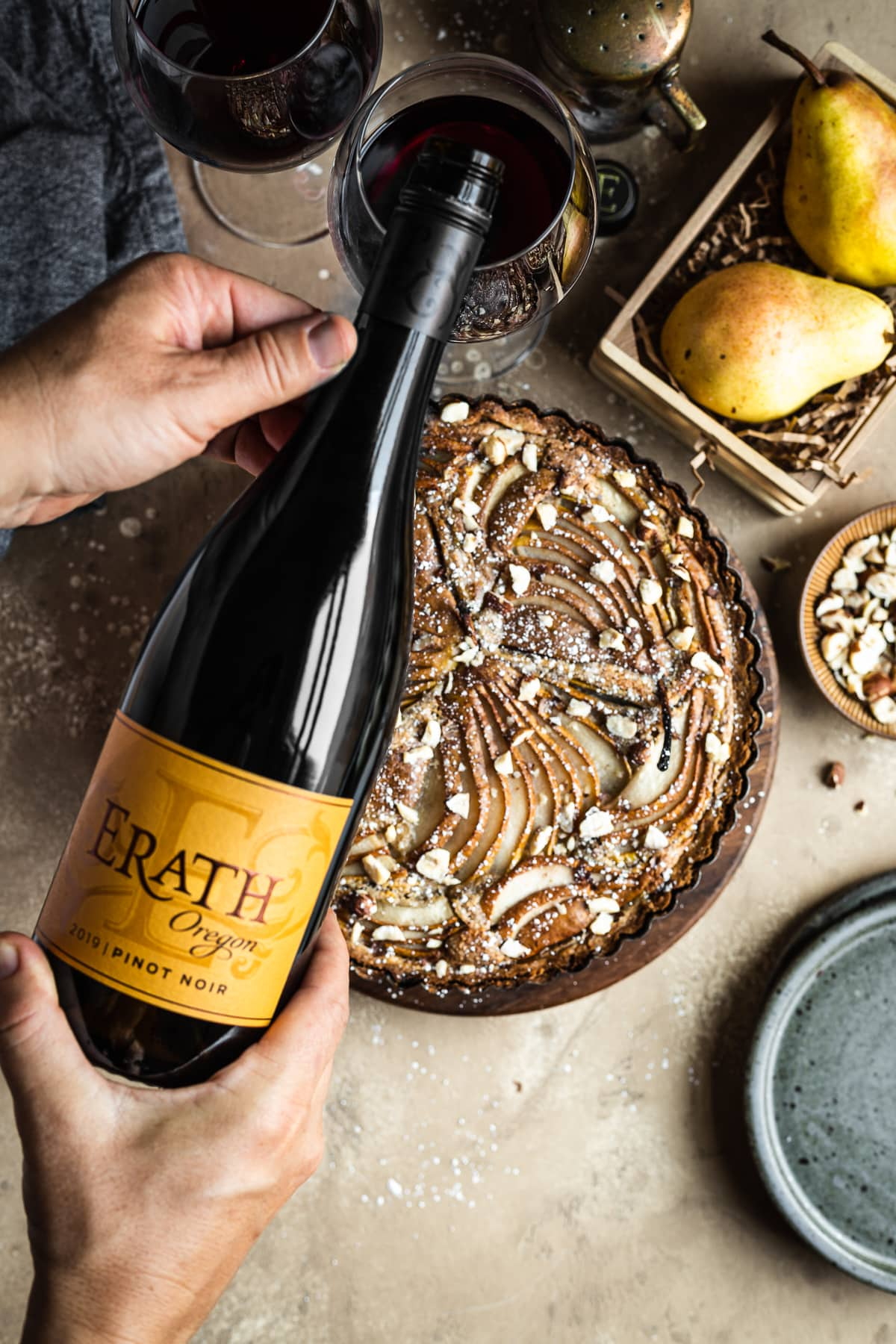 Hands pouring a bottle of red wine into glasses with a golden brown pear tart in the background. Surrounding the tart are speckled blue ceramic plates, a bowl of chopped hazelnuts, pears in a wooden crate, and a linen napkin. Everything rests on a textured tan background.