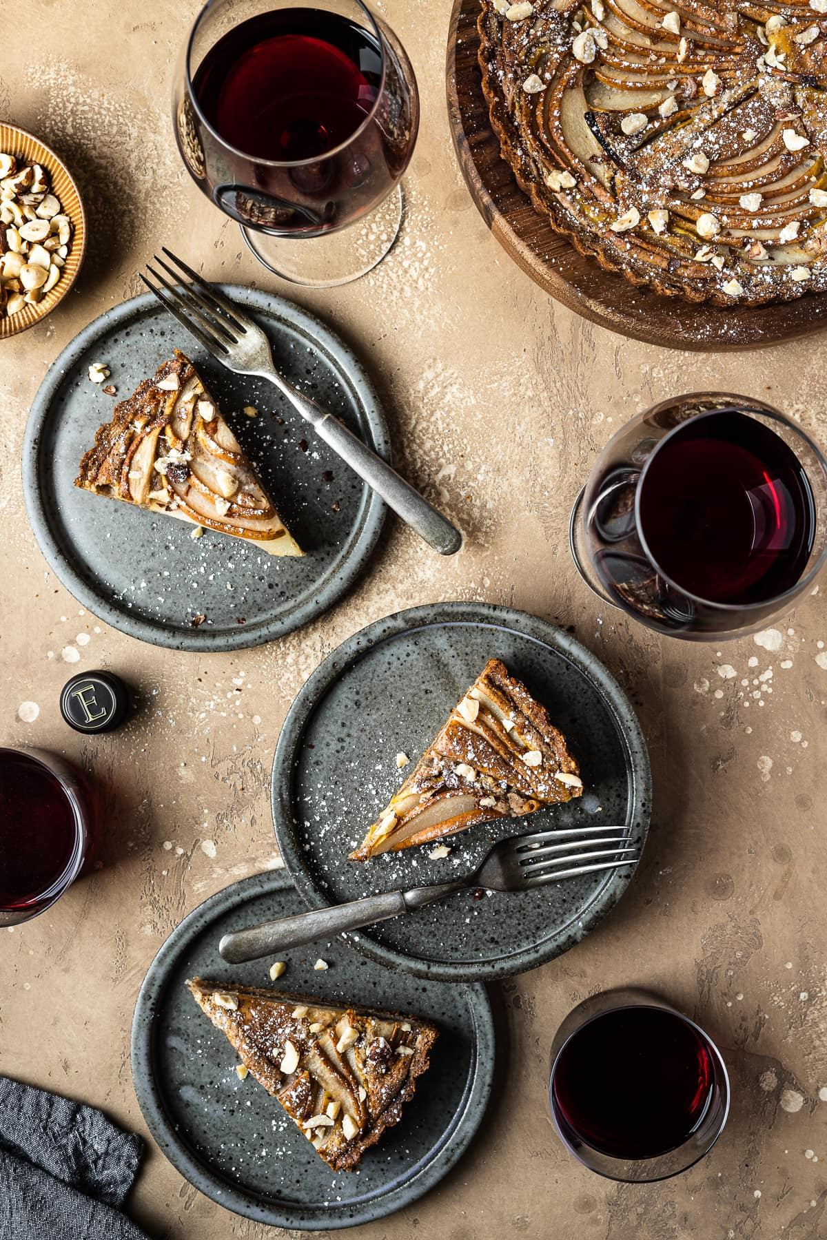 Three pear hazelnut tart slices on speckled grey blue ceramic plates. Vintage forks rests on the right side of the slices. The plates are on a warm tan textured stone background. A small bit of a textured grey napkin peeks out from the bottom left corner, and a small view of a bowl of chopped hazelnuts is visible at top left. There are four full glasses of red wine arranged throughout the image. The remainder of the tart is at top right.