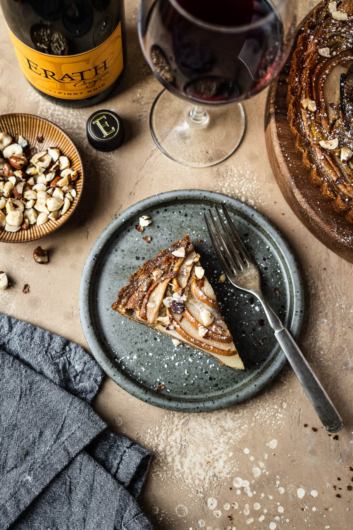 Pear hazelnut tart slice on a speckled grey blue ceramic plate. A vintage fork rests on the right side of the plate. The plate is on a warm tan textured stone background. A textured grey napkin is at the bottom left corner, and a small bowl of chopped hazelnuts is visible at top left along with a wine bottle and a glass of red wine at top. The remainder of the tart peeks out at top right.