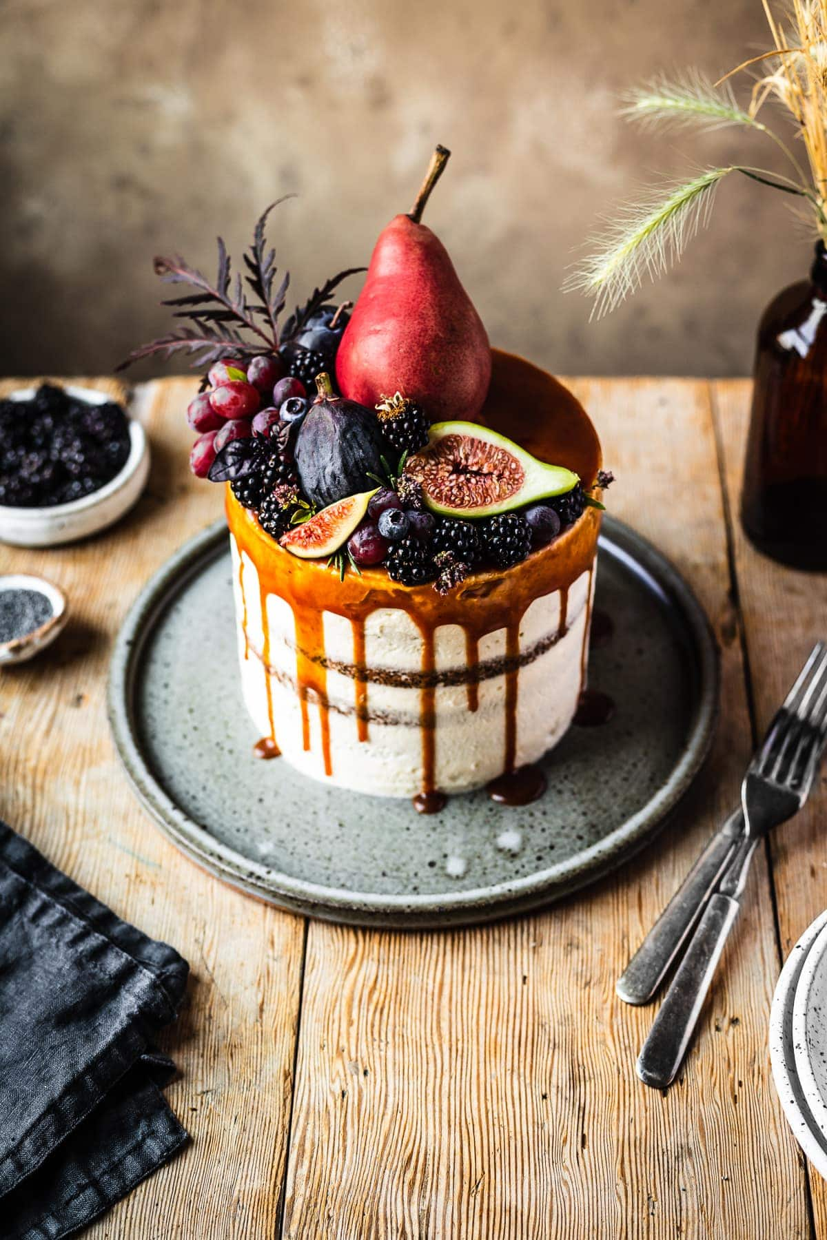 A 45 degree angle view of a layer cake with a caramel drip and a crown of late summer fruit on top. The cake sits on a blue grey ceramic platter on a rustic wooden table with forks, a dark blue linen napkin, and small bowls of poppy seeds and blackberries nearby. There is a warm tan stone background behind the table.