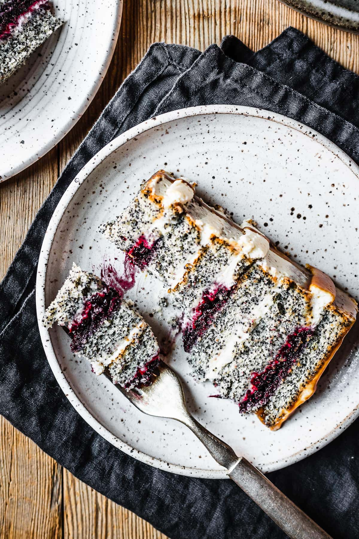 A slice of poppyseed cake with mascarpone frosting and caramel drip, with layers of vibrant purple blackberry basil jam. The slice sits on a white speckled ceramic plate with a navy blue linen napkin folded underneath, on a rustic wooden table.