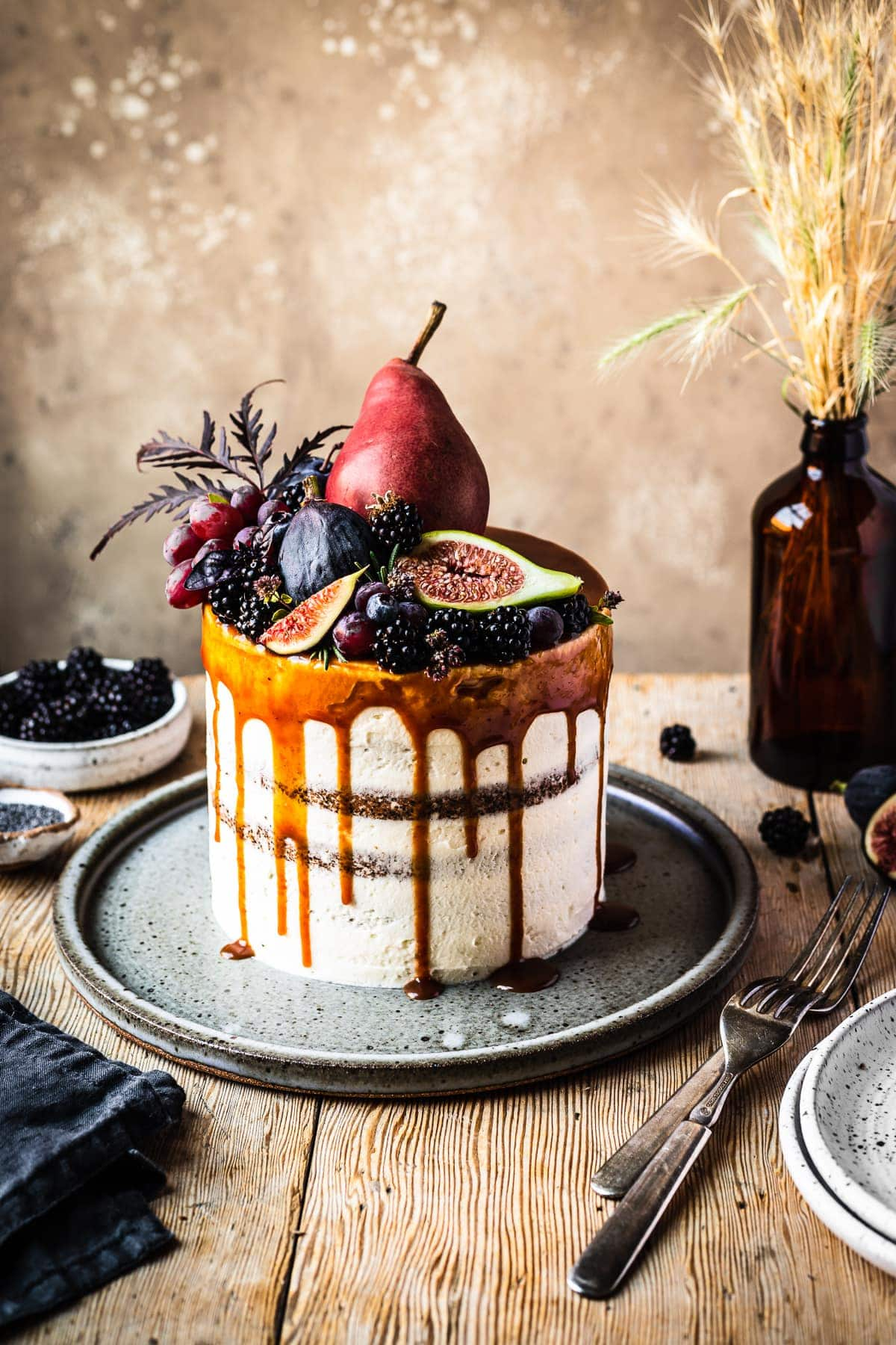 A white frosted cake with a caramel drip and a crown of late summer fruit on top. The cake sits on a blue grey ceramic platter on a rustic wooden table with forks and small bowls of poppy seeds and blackberries nearby. There is a warm tan stone background behind the table.