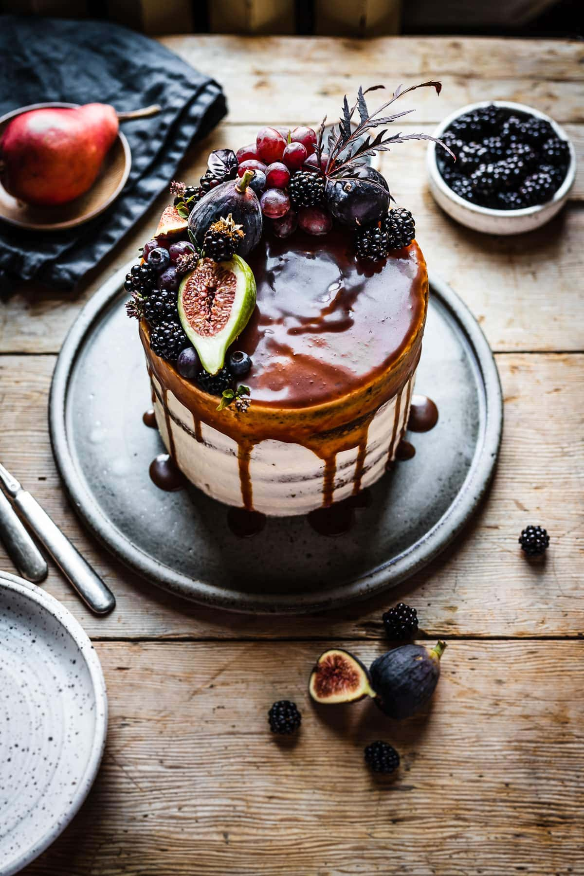 A white frosted layer cake with a caramel drip and a crown of late summer fruit on top. The cake sits on a blue grey ceramic platter on a rustic wooden table with forks and small bowls of poppy seeds and blackberries nearby. The light is coming from behind the cake and makes the caramel on top of the cake shine.