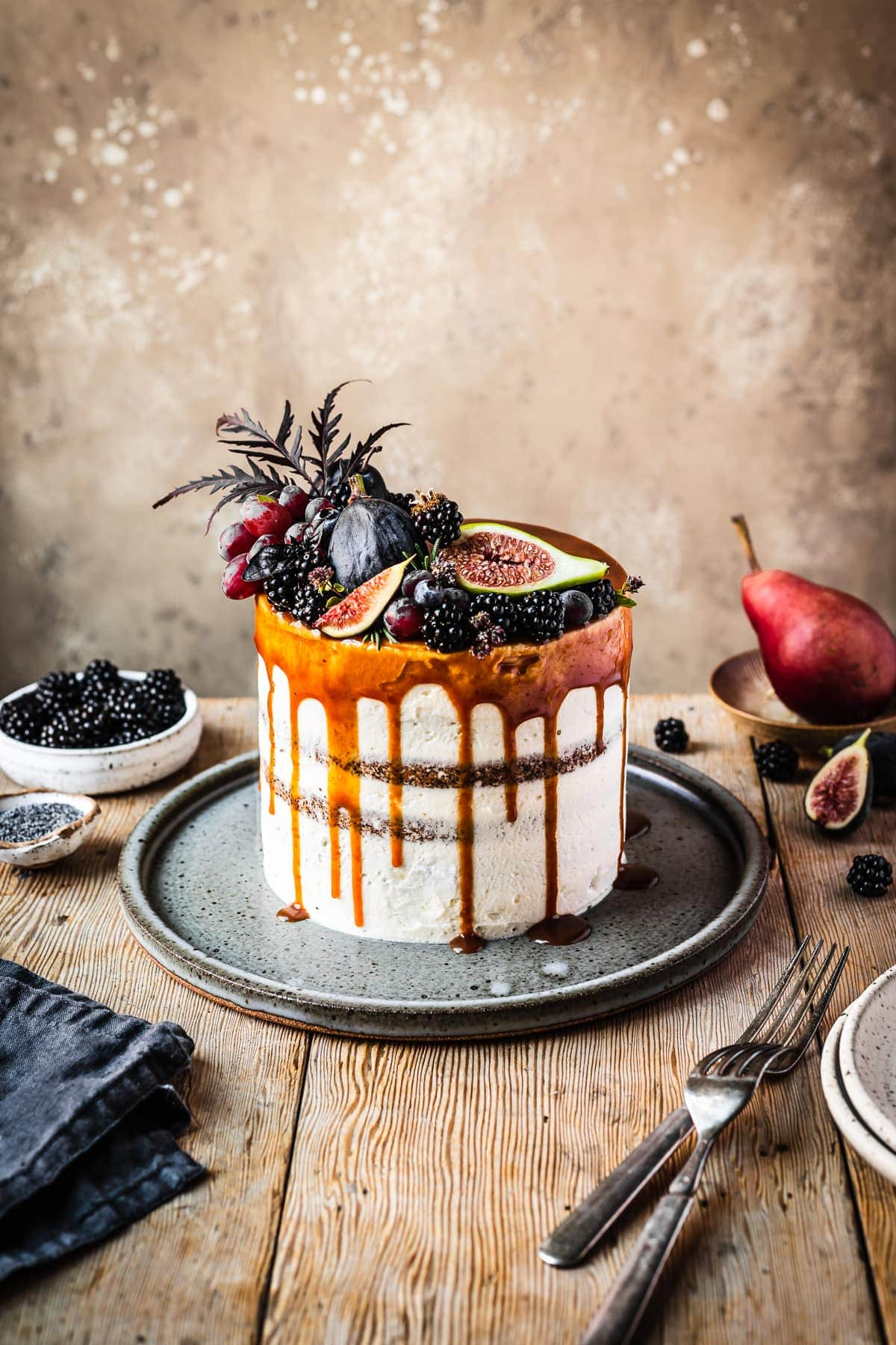 A white frosted blackberry poppy seed layer cake with a caramel drip and a crown of late summer fruit on top. The cake sits on a blue grey ceramic platter on a rustic wooden table with forks and small bowls of poppy seeds and blackberries nearby. There is a warm tan stone background behind the table.