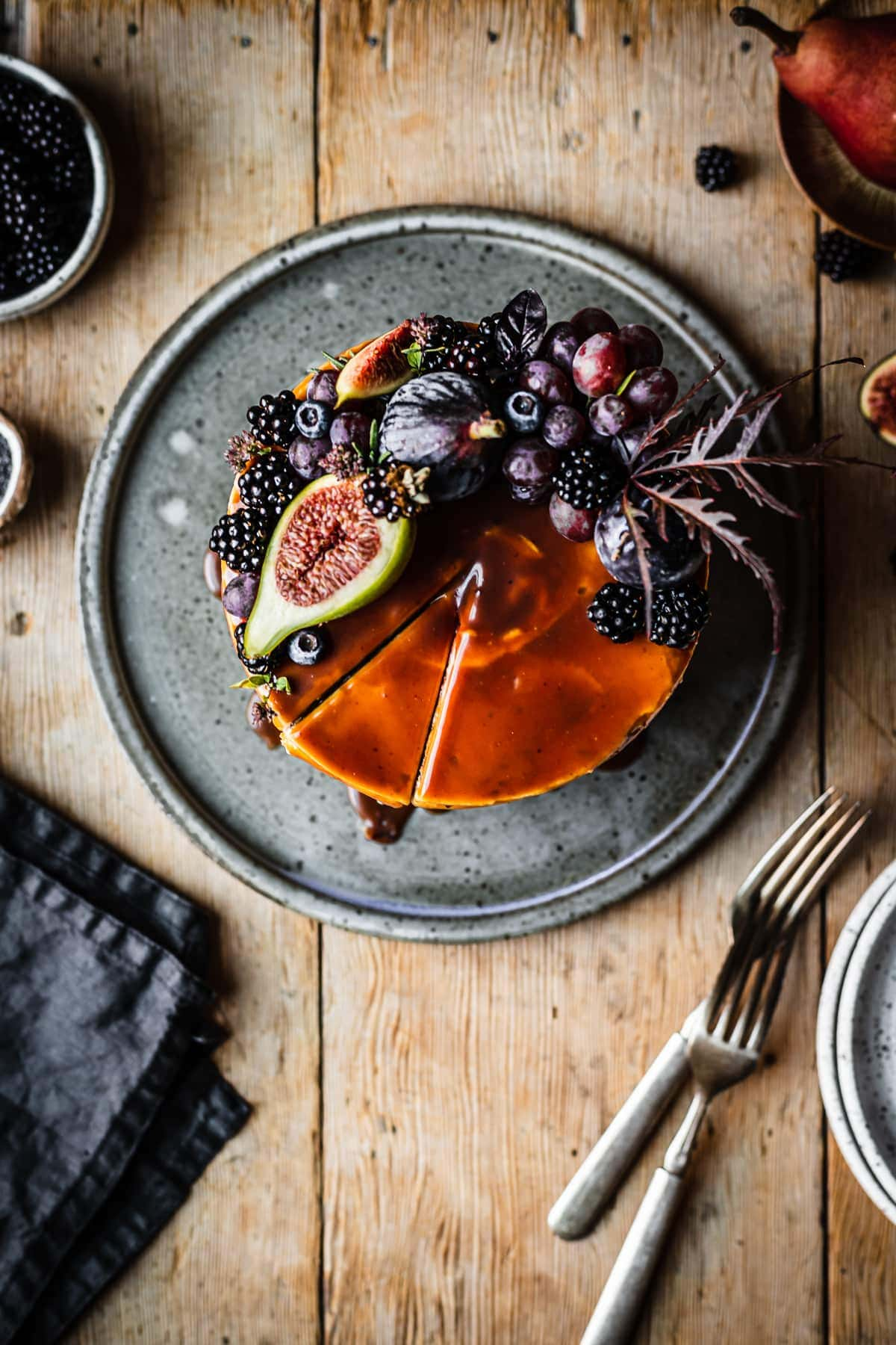 Top view of a cake topped with caramel and a crescent shaped crown of late summer fruit, including figs, blackberries and grapes. A slice of cake has been cut but not removed. The cake sits on a blue grey ceramic platter on a rustic wooden table with forks, a dark blue napkin, and small bowls of poppy seeds and blackberries nearby.