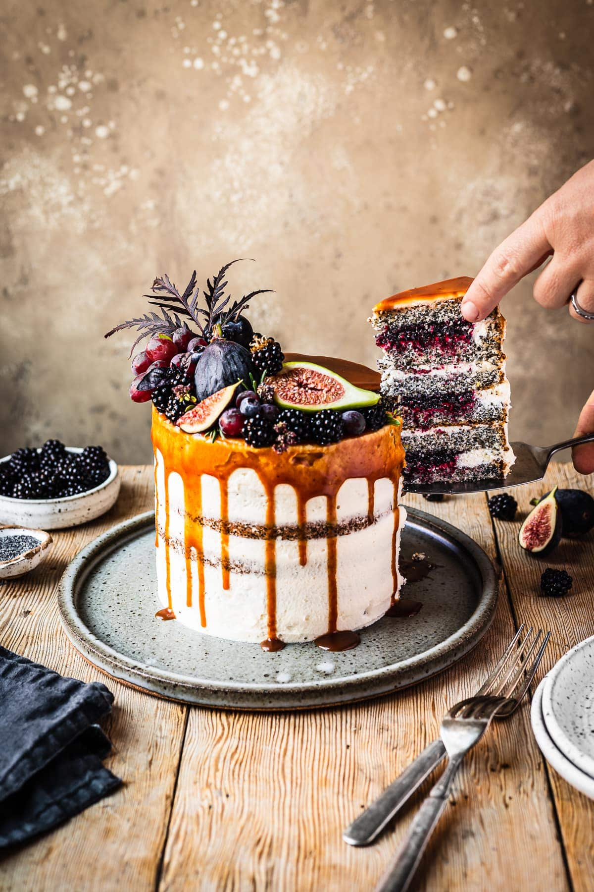A white frosted layer cake with a caramel drip and a crown of late summer fruit on top. Hands are removing a slice balanced on a cake server, revealing layers of poppy seed cake, vibrant purple jam and white frosting. The cake sits on a blue grey ceramic platter on a wooden table with forks and small bowls of poppy seeds and blackberries nearby. There is a warm tan stone background behind the table.