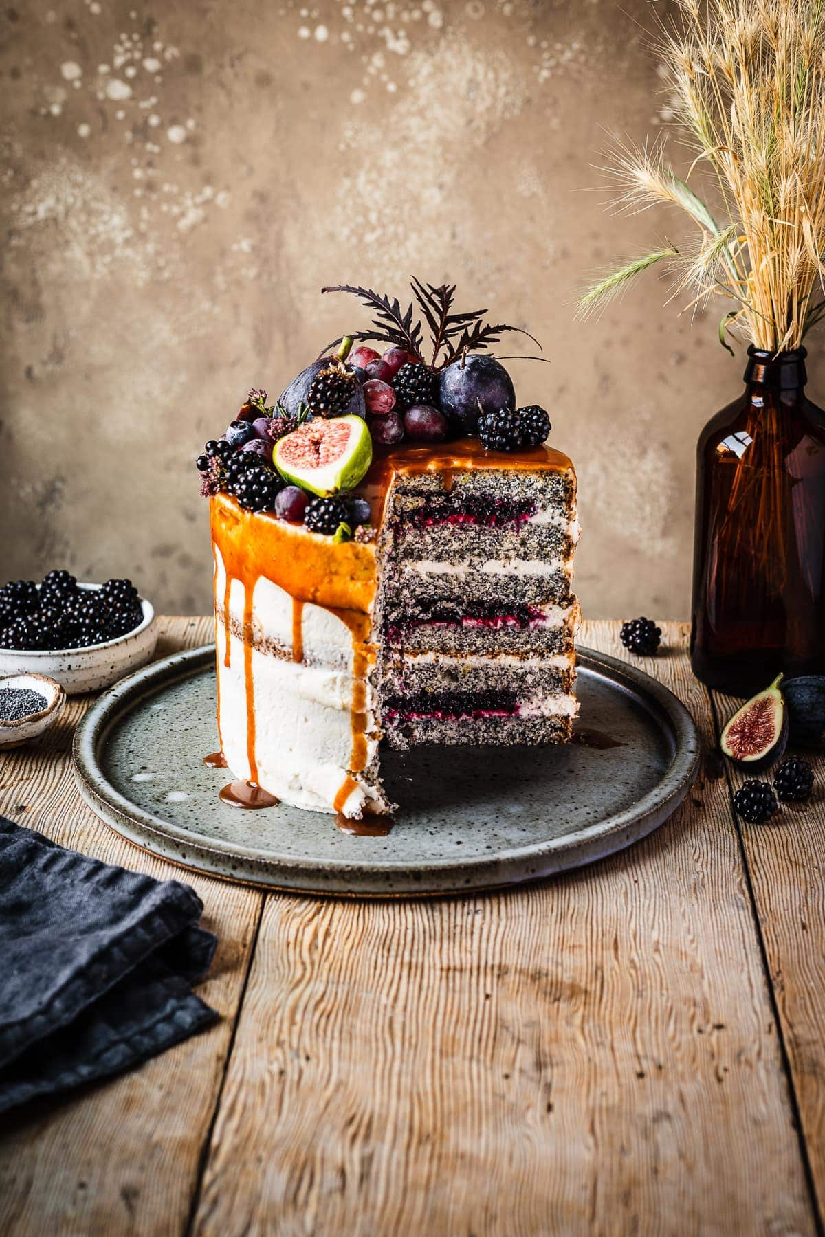 A cross section of a white layer cake with a caramel drip and a crown of late summer fruit on top. Slices are missing, revealing layers of poppy seed cake, vibrant purple jam and white frosting. The cake sits on a blue grey ceramic platter on a wooden table with forks and small bowls of poppy seeds and blackberries nearby. There is a warm tan stone background behind the cake and table.