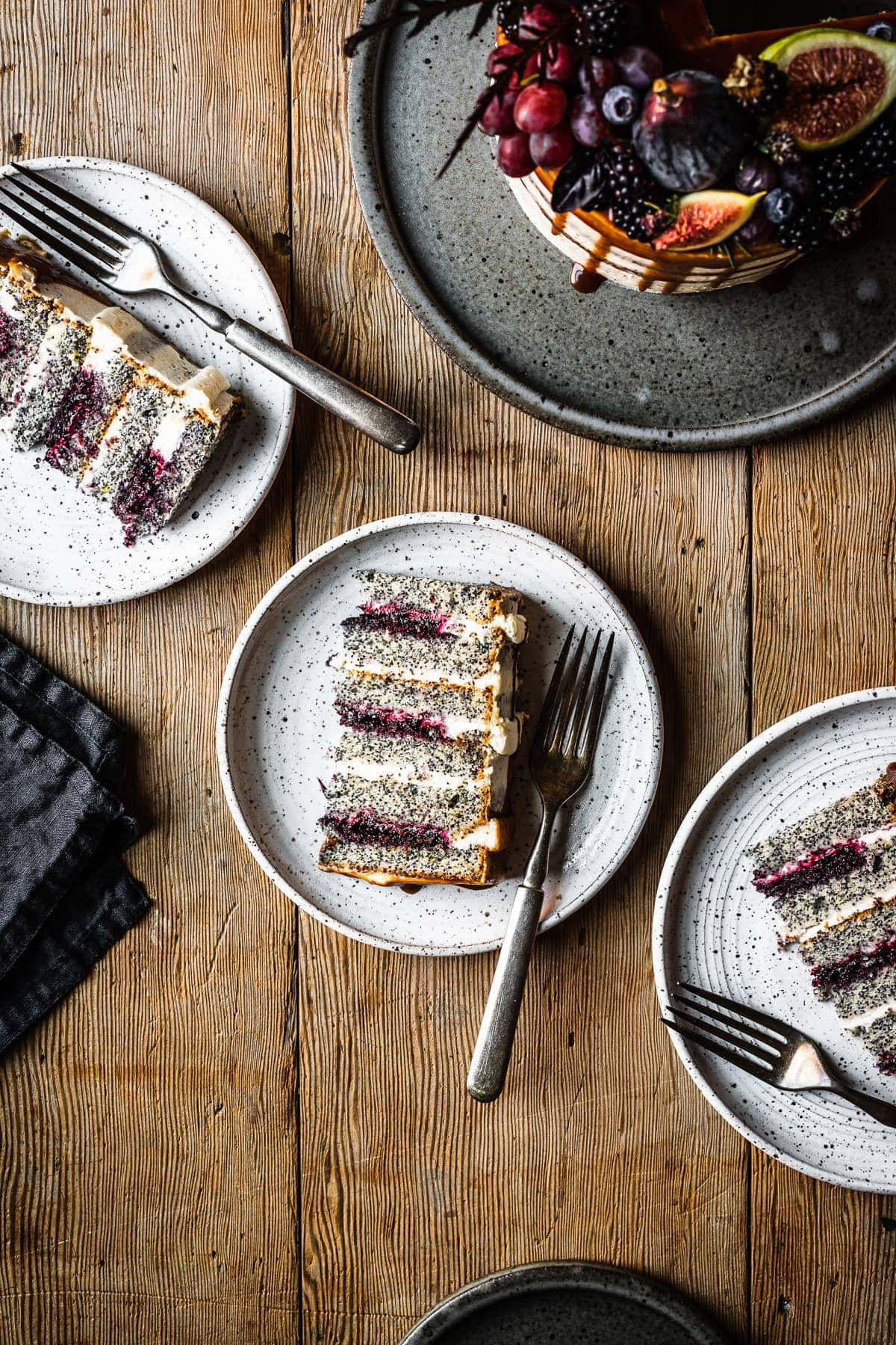 Three speckled white ceramic plates with slices of blackberry poppy seed cake on a rustic wooden table. The rest of the cake, decorated with late summer figs, blackberries, blueberries and grapes, sits on a blue grey ceramic platter at the top right of the image.