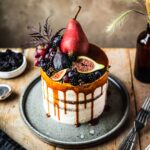 A white layer cake with a caramel drip and a crown of late summer fruit on top. The cake sits on a blue grey ceramic platter on a wooden table with forks and small bowls of poppy seeds and blackberries nearby.