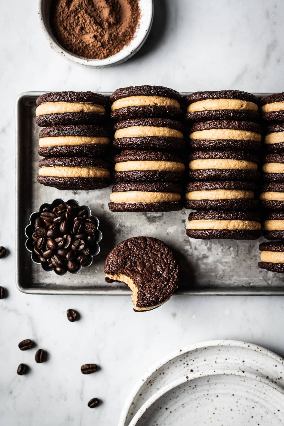 A silver metal cookie sheet holds four tidy rows of frosting filled sandwich cookies on end to show their centers. One is lying flat with a bite taken out of it. The cookie sheet is on a white marble surface. Two speckled white ceramic plates, a small fluted container of coffee beans, and a small white ceramic bowl of cocoa powder are on the border of the image.