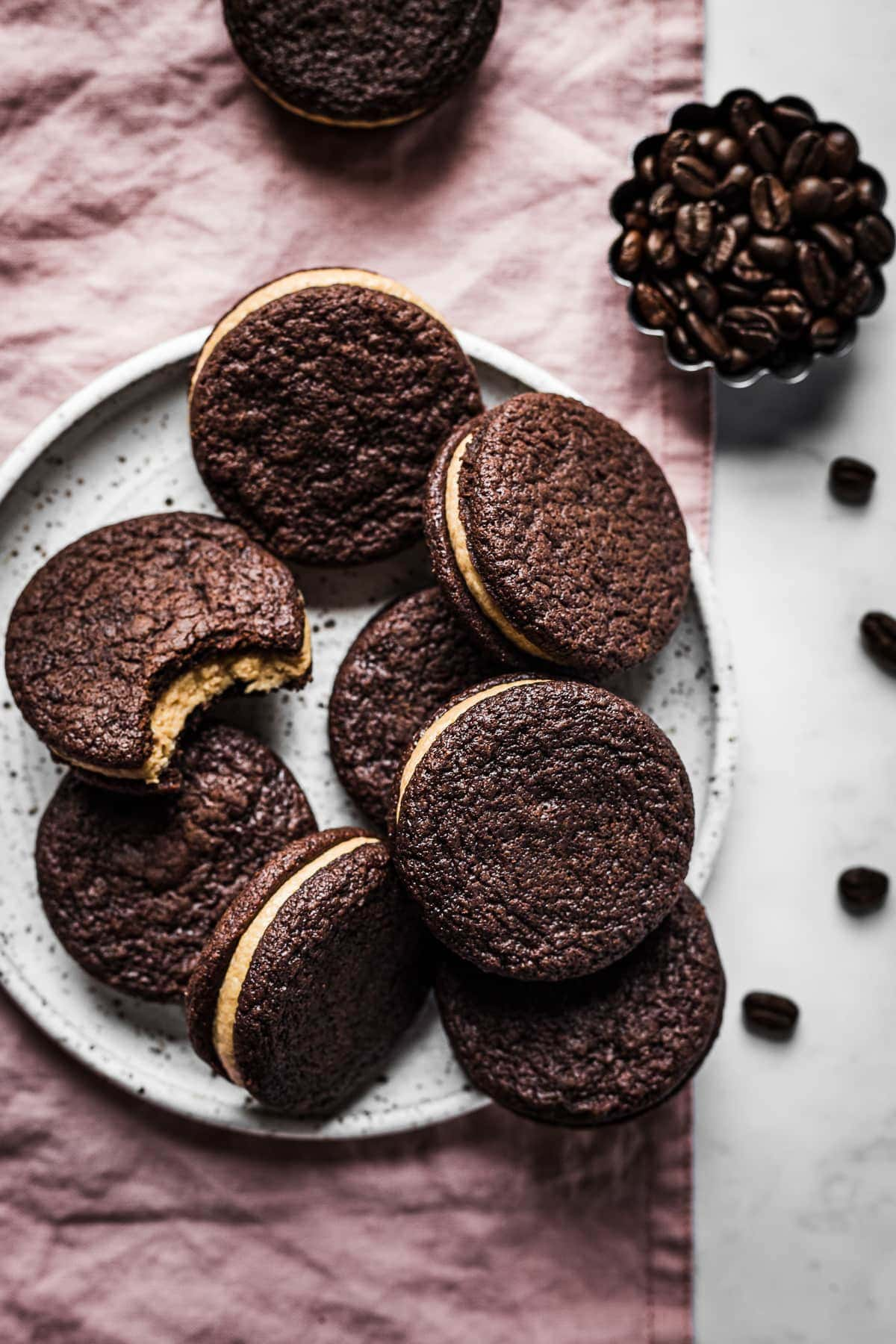 A pile of chocolate cookies on a speckled white ceramic plate on a pink linen surface. Nearby are more cookies and a small fluted container of coffee beans. One cookie has a bite taken out of it, revealing the coffee mascarpone frosting.