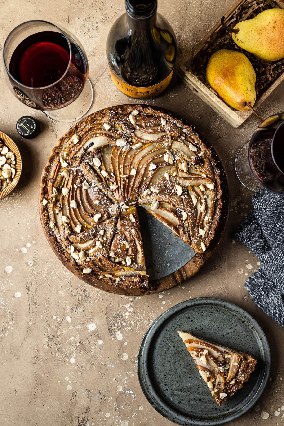 A golden brown pear tart with a slice cut out and resting on a blue grey ceramic plate nearby. Surrounding the tart are a bowl of chopped hazelnuts, pears in a wooden crate, a wine bottle and two wine glasses filled with red wine, and a dark blue linen napkin. Everything rests on a textured tan background.