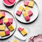 Cornmeal bars dipped in pink glaze on white plates and white parchment squares