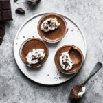 Three chocolate desserts topped with whipped cream rest on a round white plate. There is a bite missing from one of the containers. A spoon and some chopped chocolate rest nearby on a grey stone surface.