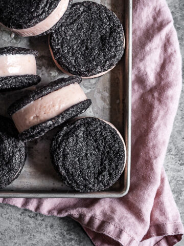 Chocolate cookies sandwich pink hued ice cream. There are six ice cream sandwiches on a vintage metal baking sheet. Tucked under the baking sheet is a pink linen napkin. It all rests on a grey stone surface.