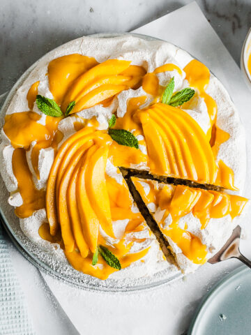 A coconut cake with baked meringue is decorated with vibrant yellow mango slices and mango puree. It rests on a white parchment square on a marble surface. A slice is being lifted out with a cake server.