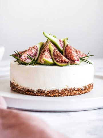 A small cheesecake on a white platter, topped with figs and rosemary, resting on a white marble surface. There is a pink napkin out of focus in the foreground.