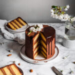A golden layer cake with dark chocolate buttercream sits on a white ceramic plate with two slices cut out of the cake, revealing the layers. The cake rests on a white marble surface with the two slices on plates nearby.