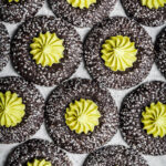 Chocolate thumbprint cookies rolled in sparkling sanding sugar, filled with a bright green piped mint matcha buttercream center.